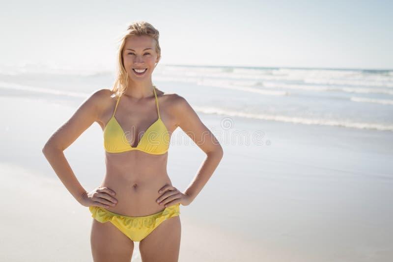 Portret van glimlachende jonge vrouw in gele bikini die zich bij strand bevinden stock afbeelding