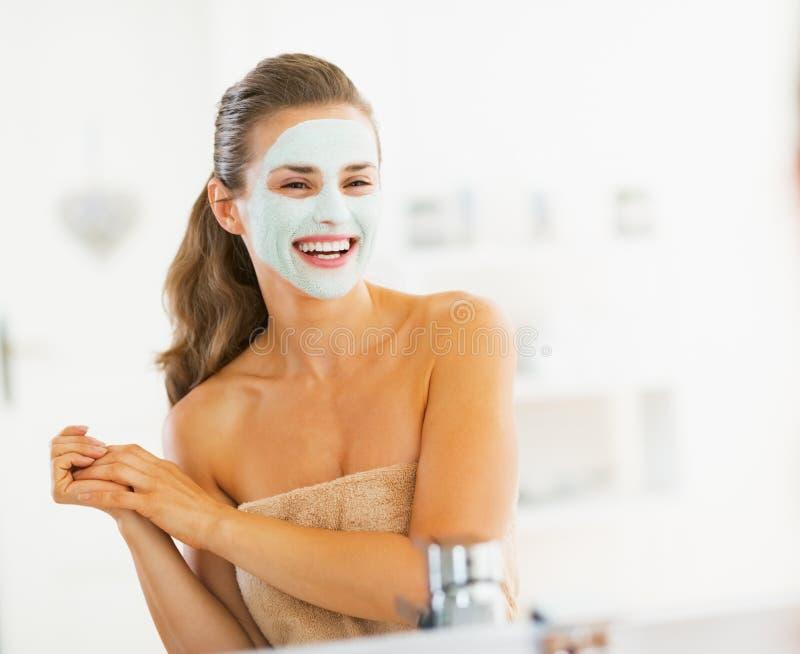 Portret van glimlachende jonge vrouw met kosmetisch masker op gezicht stock afbeelding