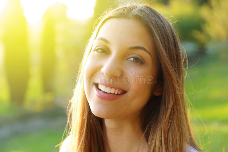 Portret van glimlachende jonge vrouw met zonlichtgloed royalty-vrije stock afbeelding