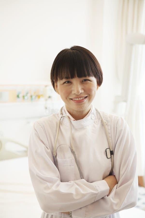 Portret van glimlachende jonge vrouwelijke die arts met wapens in het ziekenhuis worden gekruist stock afbeeldingen