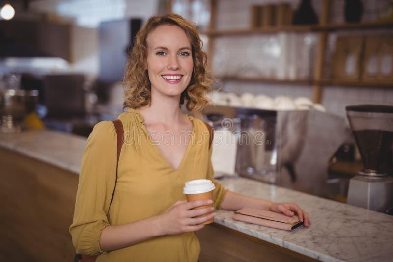 Portret van glimlachende jonge vrouwelijke klant die beschikbare koffiekop houden bij teller stock afbeeldingen
