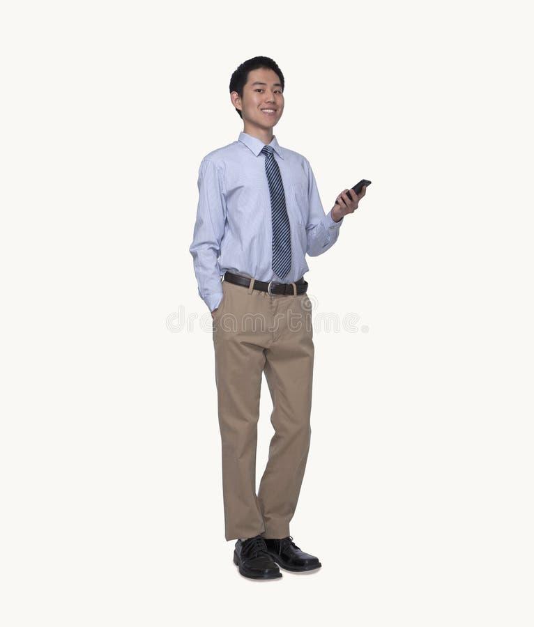 Portret van glimlachende jonge zakenman die zijn telefoon, volledige lengte, studioschot met behulp van royalty-vrije stock afbeeldingen