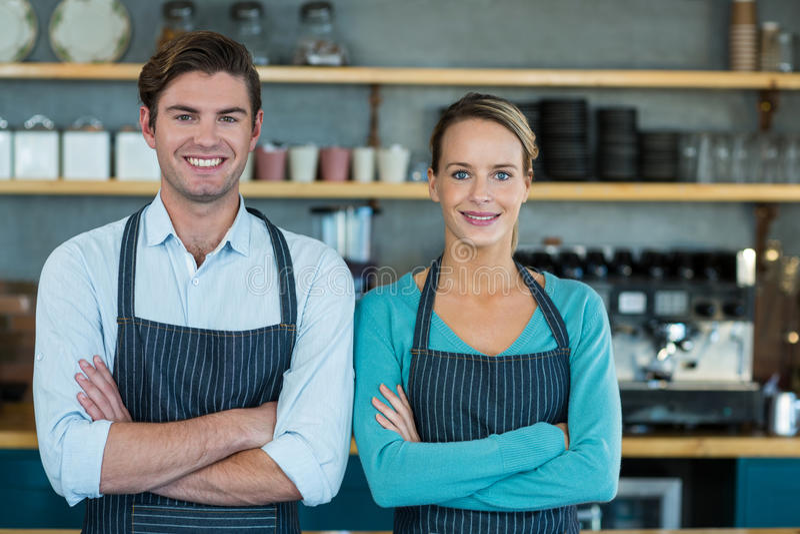 Portret van glimlachende kelner en serveerster die zich met gekruiste wapens bevinden royalty-vrije stock foto's