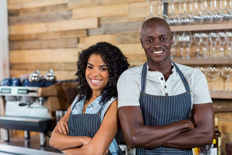 Portret van glimlachende kelner en serveerster die zich rijtjes bij teller bevinden royalty-vrije stock afbeeldingen