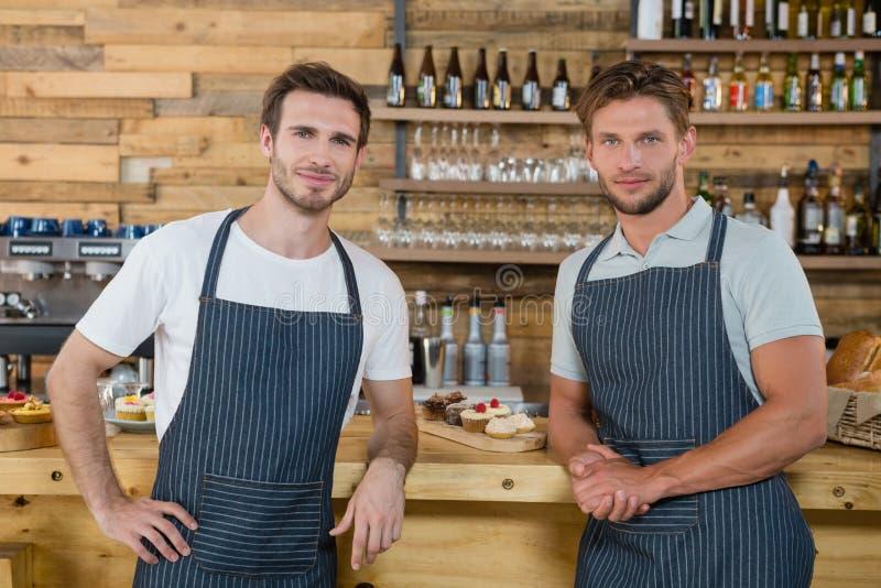 Portret van glimlachende kelners die zich bij teller bevinden royalty-vrije stock afbeelding