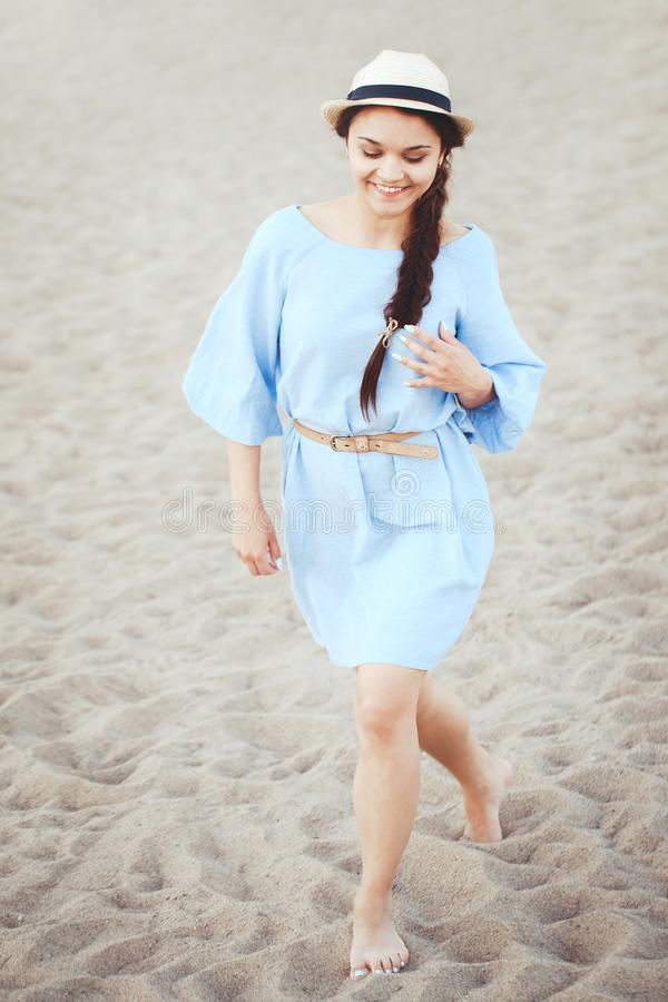 Portret van glimlachende lachende witte Kaukasische donkerbruine vrouw met gelooide huid in blauwe kleding en strohoed die op zan stock fotografie