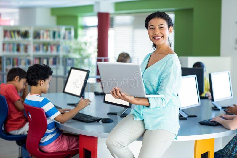 Portret van glimlachende leraar die laptop met behulp van stock afbeelding
