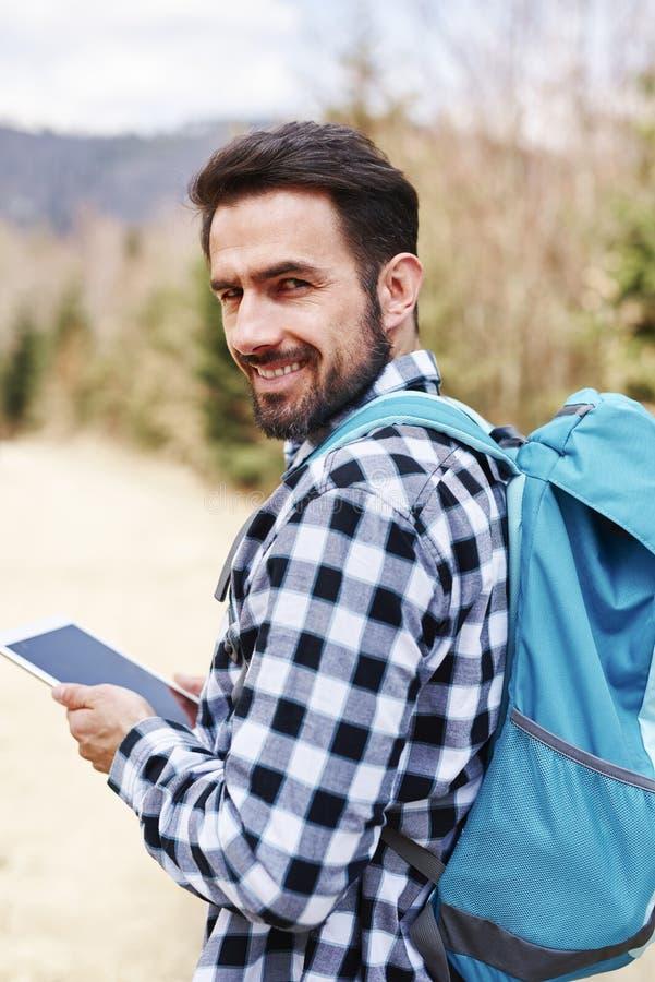 Portret van glimlachende mannelijke wandelaar met rugzak stock fotografie