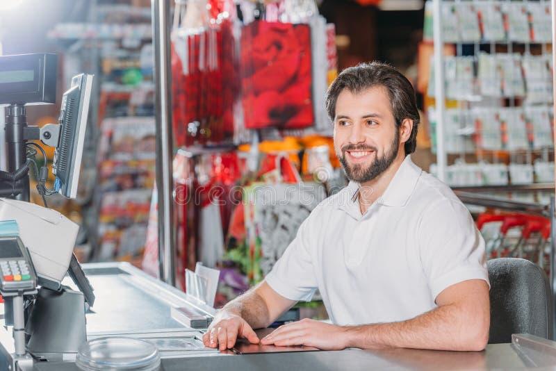 portret van glimlachende mannelijke winkelmedewerker op contant geldpunt stock foto's
