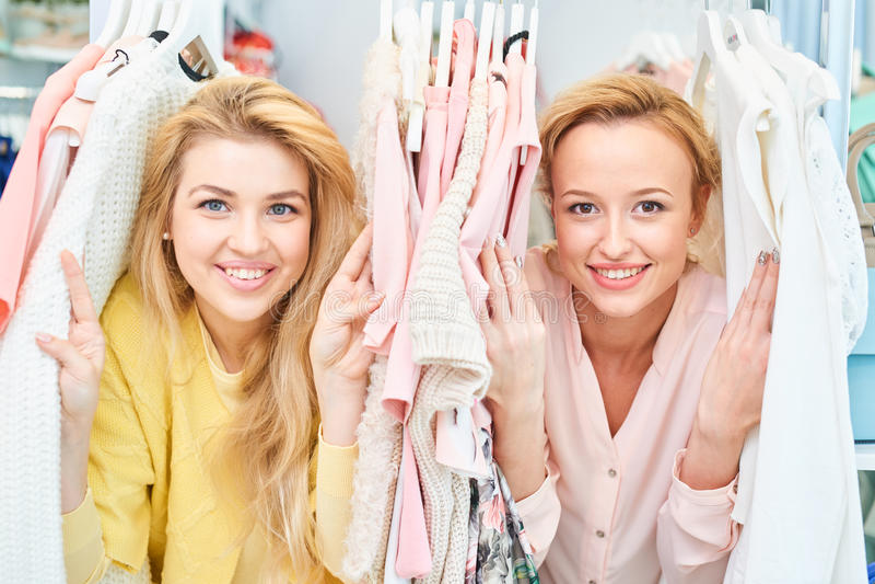 Portret van glimlachende meisjes in opslag met kleren royalty-vrije stock foto's