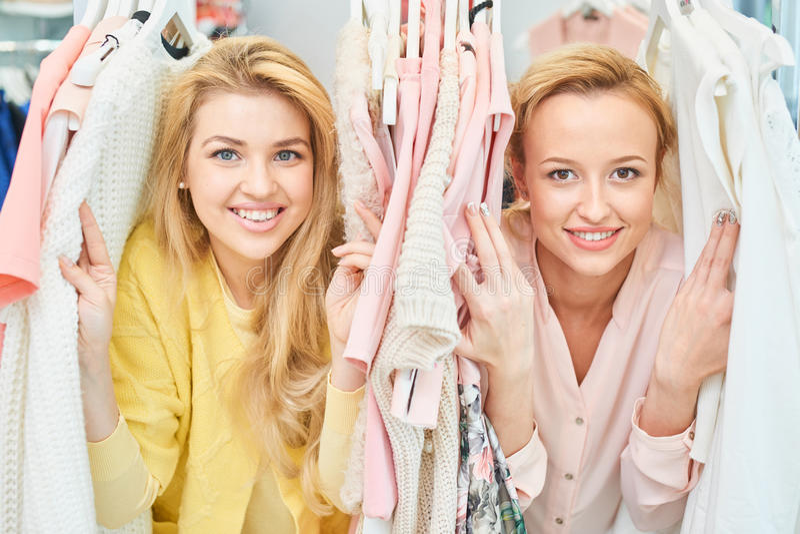 Portret van glimlachende meisjes in opslag met kleren stock afbeelding