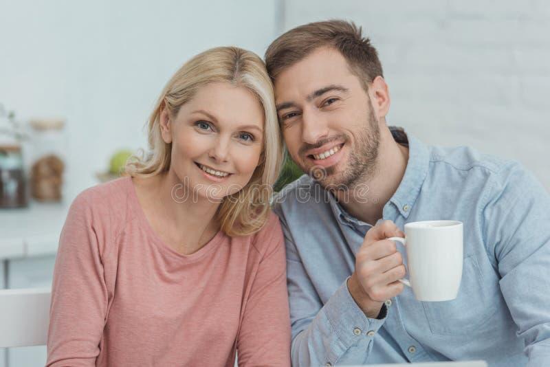 portret van glimlachende moeder en gekweekte zoon met kop van koffie het kijken stock afbeelding