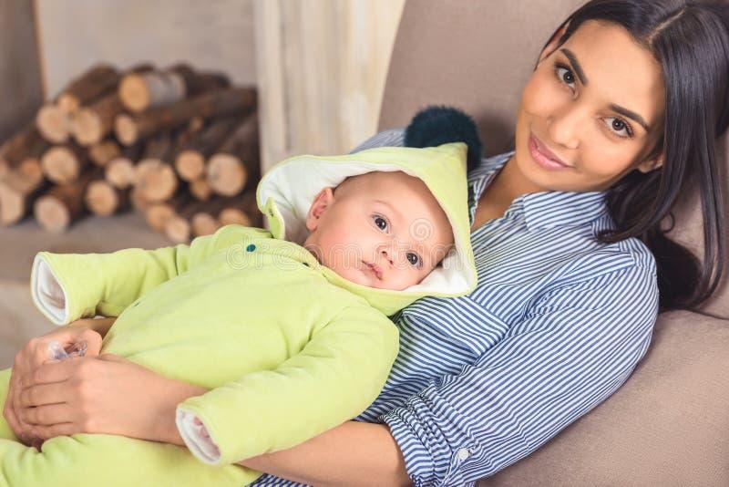 portret van glimlachende moeder met baby in handen die op bank rusten stock foto
