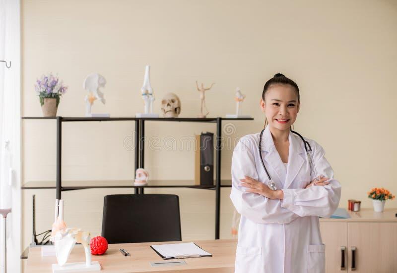 Portret van glimlachende mooie Aziatische vrouw arts status en dwarswapens die camera het ziekenhuis, het Gelukkige en positieve  royalty-vrije stock afbeeldingen