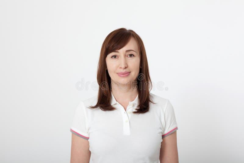 Portret van glimlachende mooie donkerbruine vrouw in lege witte t-shirt met exemplaarruimte op witte achtergrond Spot omhoog stock afbeelding