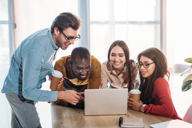 portret van glimlachende multiculturele bedrijfsmensen die aan laptop samenwerken stock afbeeldingen