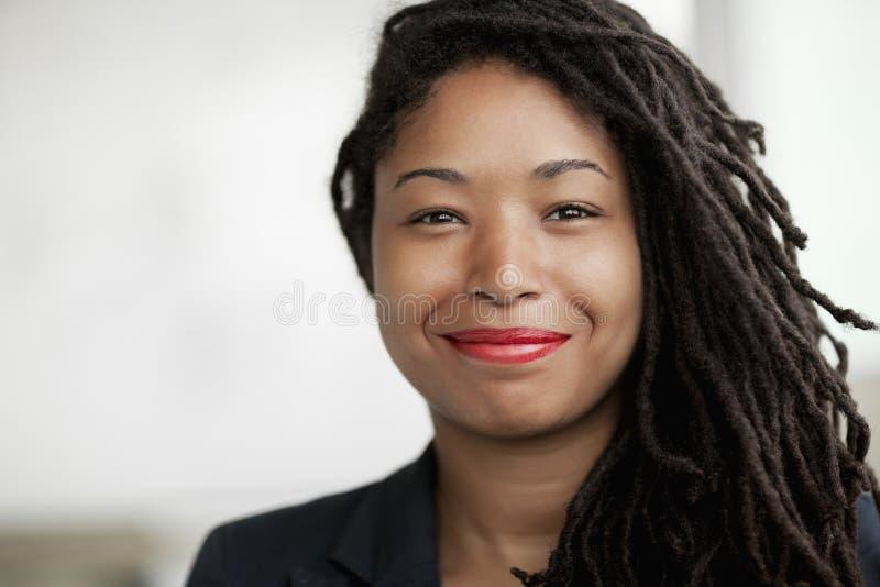 Portret van glimlachende onderneemster met dreadlocks, hoofd en schouders royalty-vrije stock fotografie