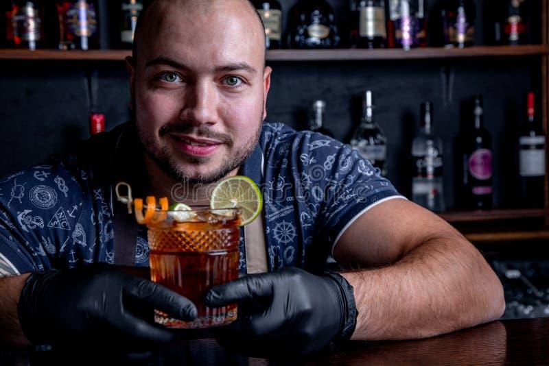 Portret van glimlachende ongeschoren barman die smakelijke alcoholvloeistof geven stock afbeelding
