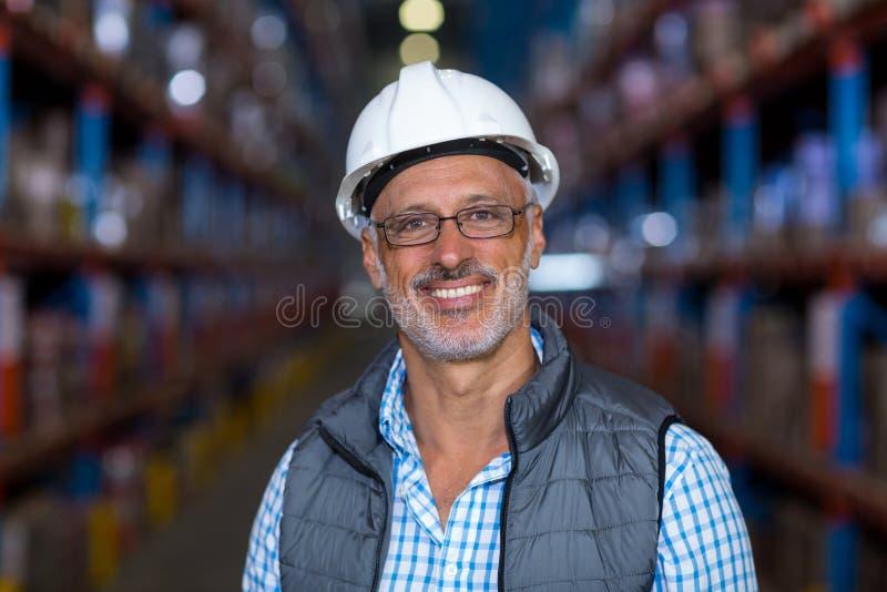 Portret van glimlachende pakhuisarbeider die bouwvakker dragen stock afbeeldingen