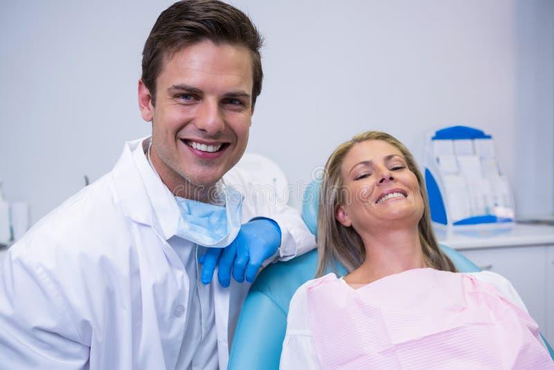 Portret van glimlachende patiënt en tandartszitting op stoel stock foto