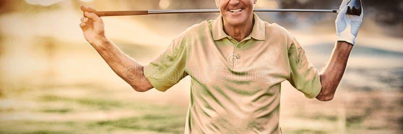 Portret van glimlachende rijpe golfspeler dragende golfclub royalty-vrije stock afbeeldingen
