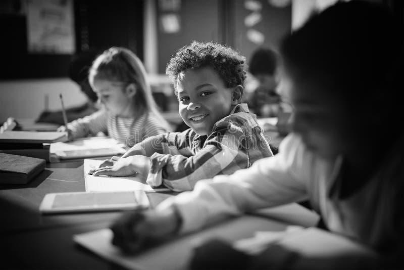 Portret van glimlachende schooljongen die zijn thuiswerk in klaslokaal doen stock fotografie