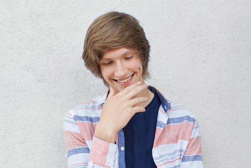 Portret van glimlachende schuwe jongen met in kapsel die toevallig overhemd dragen die onderaan holdingshand kijken op kin die ku royalty-vrije stock afbeeldingen