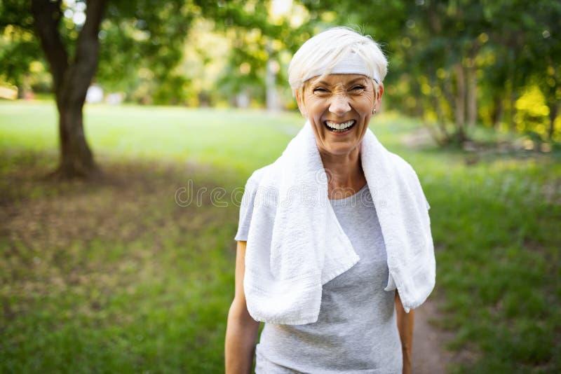 Portret van glimlachende sportieve hogere vrouw met handdoek openlucht royalty-vrije stock afbeelding
