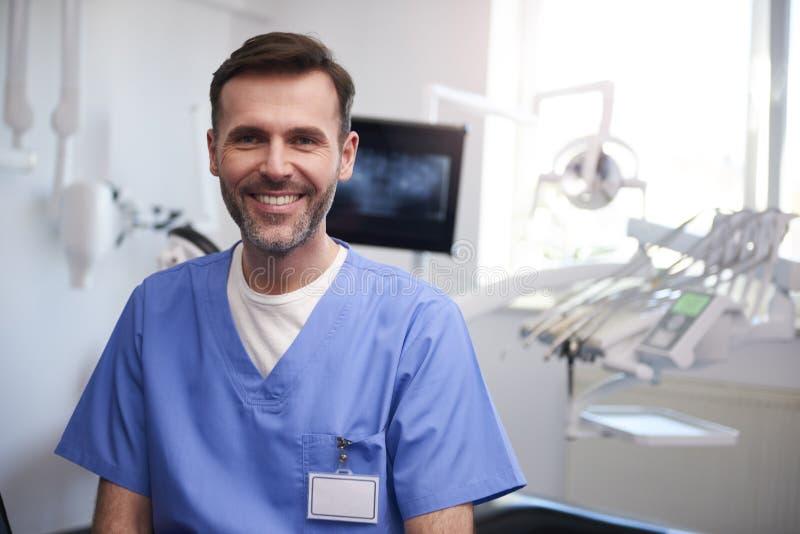 Portret van glimlachende tandarts in het bureau van de tandarts stock afbeeldingen