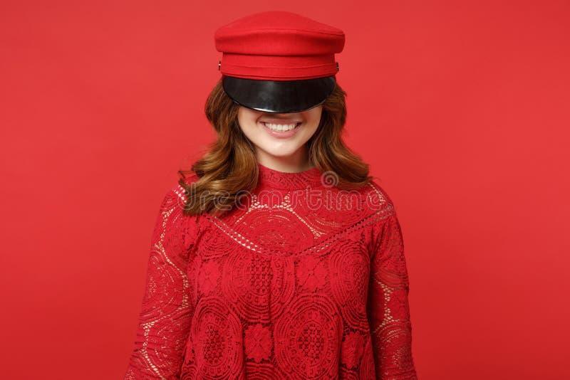 Portret van glimlachende vrolijke vrij jonge vrouw in kantkleding die ogen behandelen die met GLB op heldere rode muur wordt geïs stock afbeelding