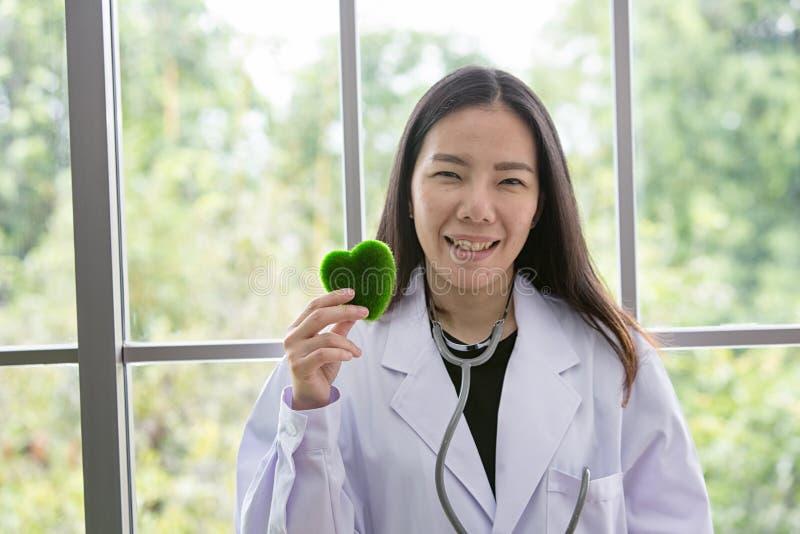 Portret van glimlachende vrouw arts met groen hart Vriendschappelijke jonge vrouwelijke arts met een stethoscoop rond op hals Azi royalty-vrije stock afbeelding