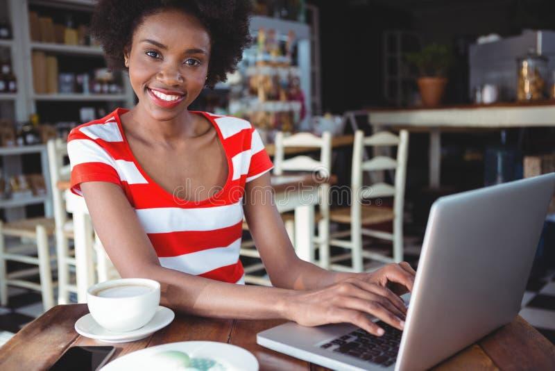 Portret van glimlachende vrouw die aan laptop werken royalty-vrije stock afbeelding
