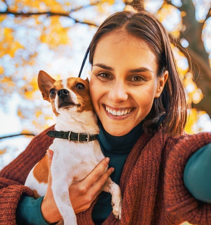 Portret van glimlachende vrouw met hond die in openlucht selfie maken royalty-vrije stock afbeeldingen