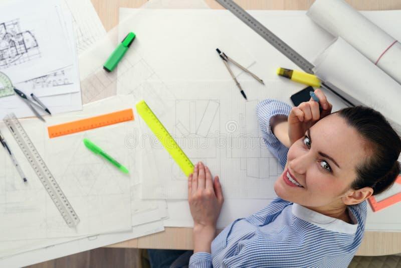 Portret van glimlachende vrouwelijke architect op de lijst met tekeningen, heersers, potloden, kompassen royalty-vrije stock afbeelding