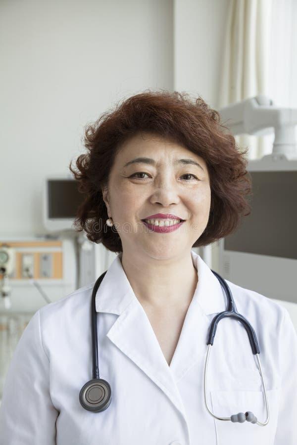 Portret van glimlachende vrouwelijke arts met een stethoscoop die camera bekijken royalty-vrije stock fotografie