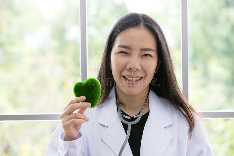 Portret van glimlachende vrouwelijke arts met groen hart Vriendschappelijk u stock foto's
