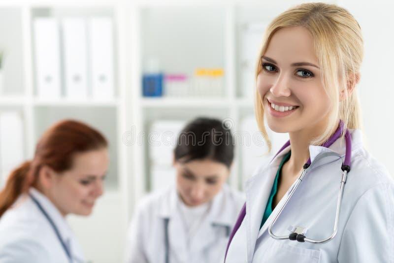 Portret van glimlachende vrouwelijke geneeskunde arts met twee collega's die bij achtergrond werken royalty-vrije stock foto