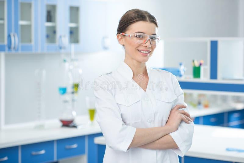 Portret van glimlachende wetenschapper in witte laag en beschermende glazen stock afbeeldingen