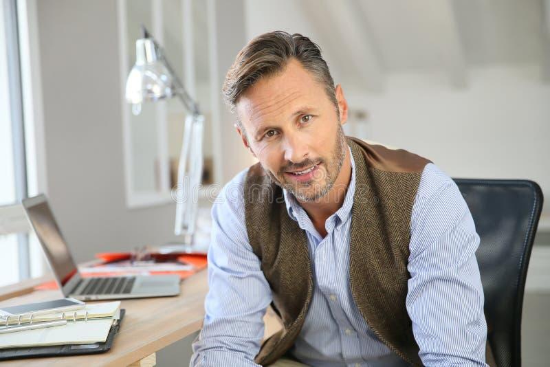 Portret van glimlachende zakenman op middelbare leeftijd op kantoor stock foto