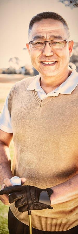Portret van golfspeler het stellen met een bal royalty-vrije stock foto's