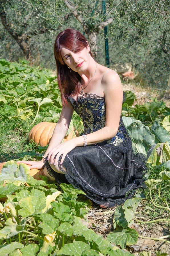 Gotische vrouw dichtbij de pompoenen royalty-vrije stock foto