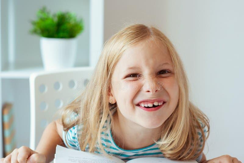 Portret van grappig weinig schoolmeisje met boeken in klaslokaal stock foto's