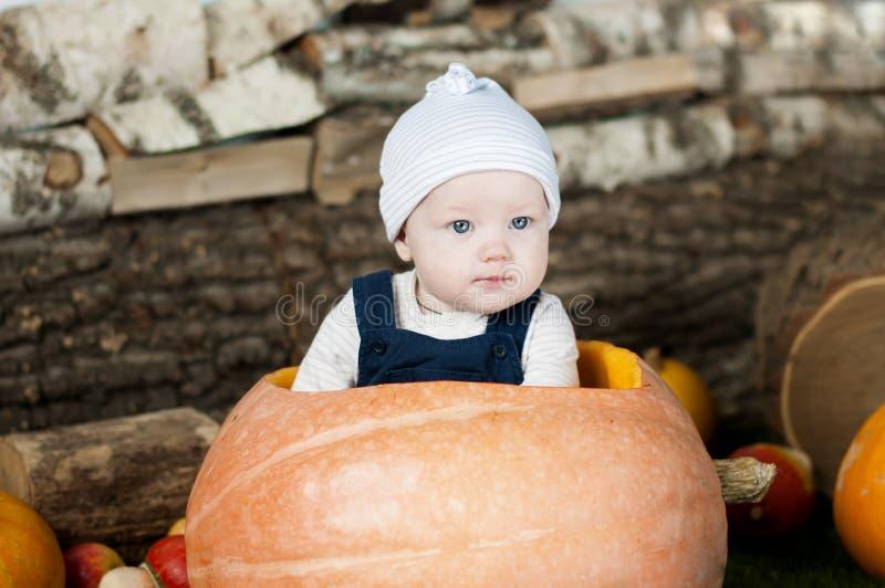 Portret van grappige baby in grote pompoen stock fotografie