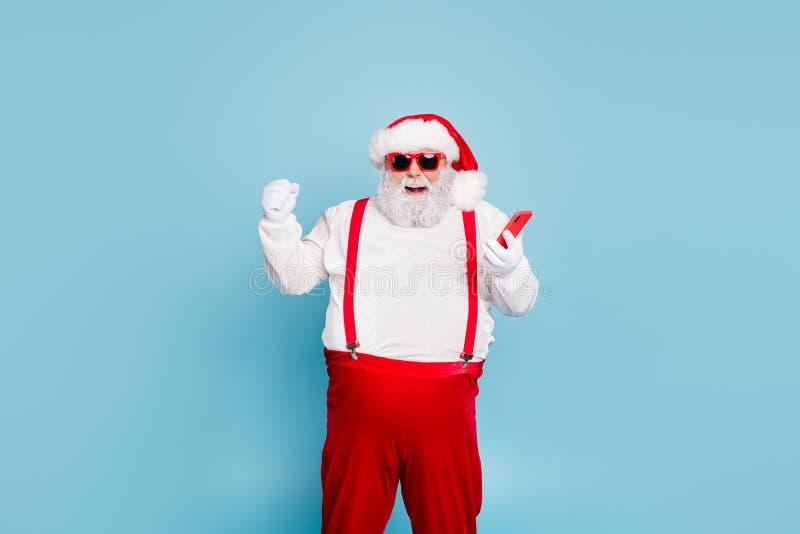 Portret van grappige bizarre kerst vader met grote buik om mobiele telefoon te gebruiken werpt vuisten op en schreeuwt ja win in  royalty-vrije stock foto