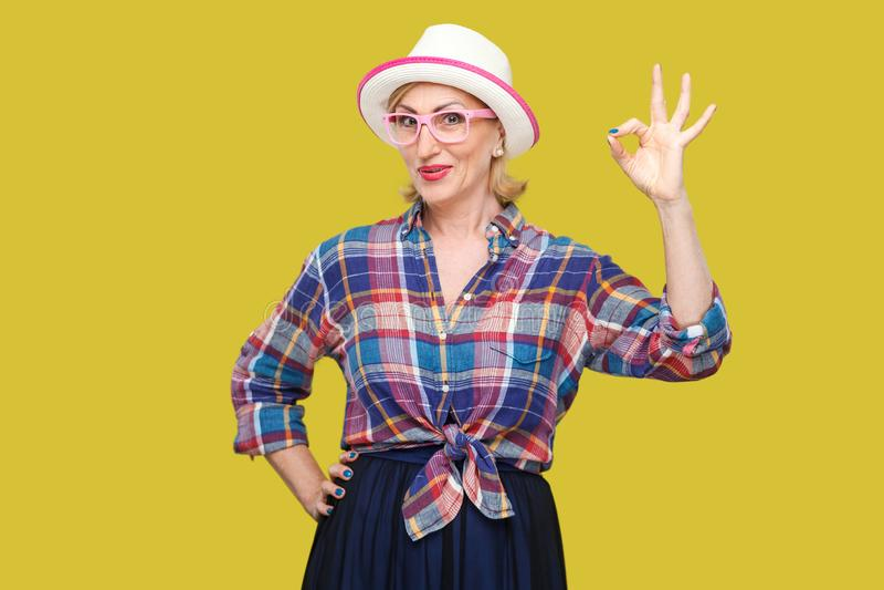 Portret van grappige gelukkige moderne leuke modieuze rijpe vrouw in toevallige stijl met hoed en oogglazen die zich met het O.k. royalty-vrije stock fotografie