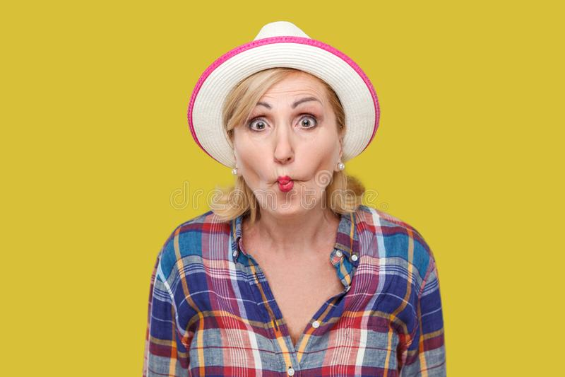 Portret van grappige geschokte moderne modieuze rijpe vrouw in toevallige stijl met witte hoed die zich met vissenlippen bevinden royalty-vrije stock afbeeldingen