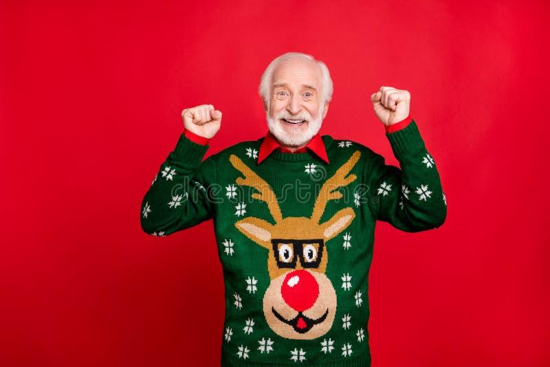 Portret van grappige, grijs-haar oude man tilt vuisten op en schreeuwt ja win kerst loterij op nieuwjaars themafeedag royalty-vrije stock fotografie