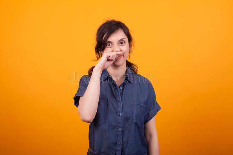 Portret van grappige jonge vrouw die haar neus na het gebruiken van schoonheidsmiddelen krassen royalty-vrije stock foto