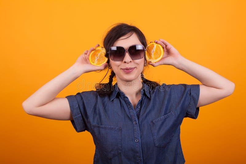 Portret van grappige jonge vrouw die sappige sinaasappelen in studio over gele achtergrond houden stock foto