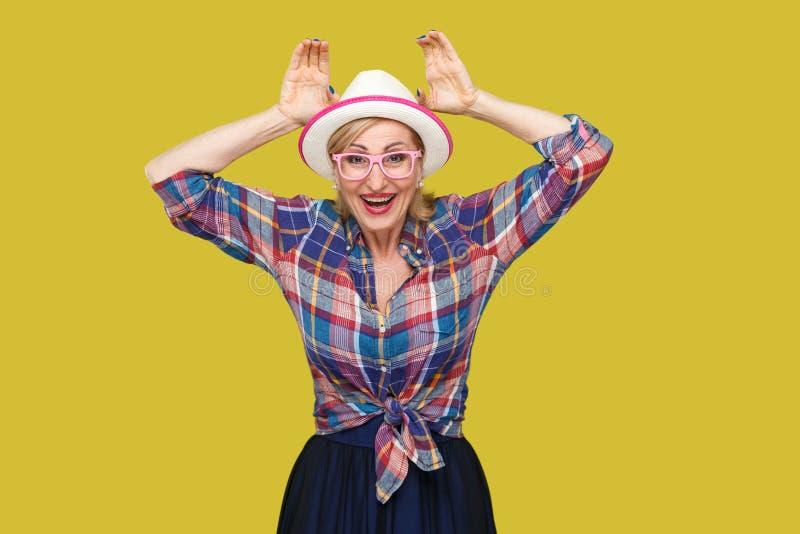 Portret van grappige moderne modieuze rijpe vrouw in toevallige stijl met hoed en oogglazen die zich met konijntjesoren gebaar en stock afbeeldingen